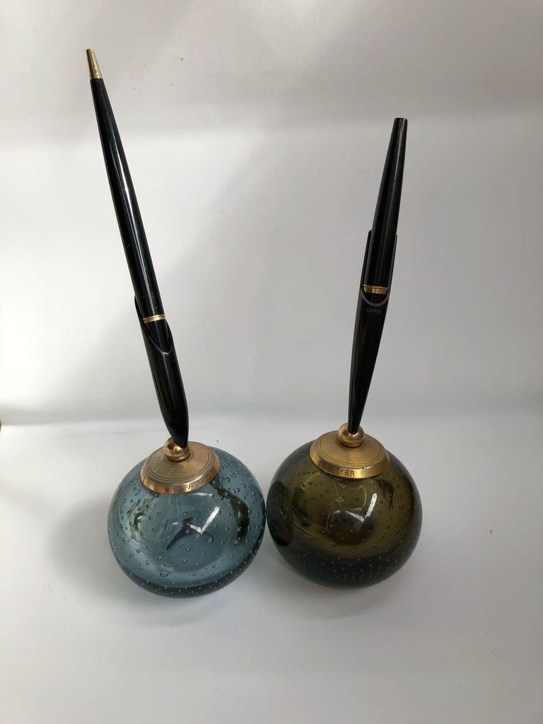 A pair of 20th century paperweight penholders made out of Whitefriars air bubbled glass in green and blue for English Parker Pen Company. The original fountain pen and ball pens come with the set, one of the pen's endings is missing - the ball pen