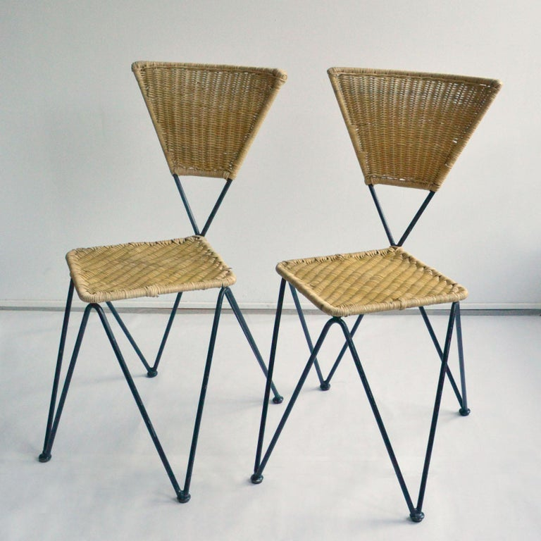 Set of 2 geometric wicker and metal dining chairs designed by Karl Fostel Erben and executed by Sonett, Vienna, circa 1950. The frame is made of black lacquered iron, the seat and back are woven in cane. These comfortable chairs can stack.  The