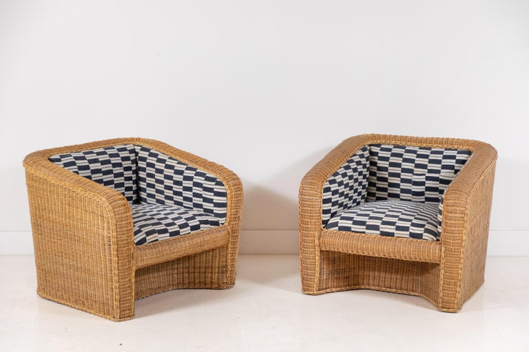 Pair of vintage wicker armchairs newly upholstered in vintage one of a kind Nigerian fabric. Please note, the African fabric is very old and has slight imperfections which adds character to the fabric, there are some patches which offer a wabi sabi