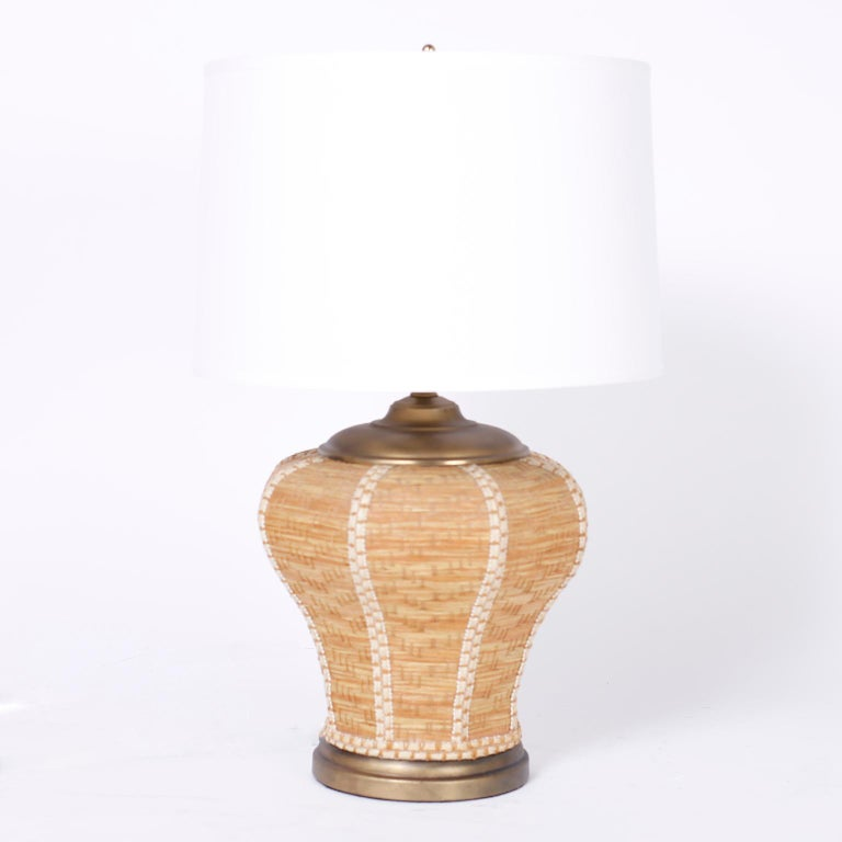 Pair of midcentury table lamps with Classic form and organic ambiance crafted in wicker with an unusual weave pattern and burnished brass caps and bases.