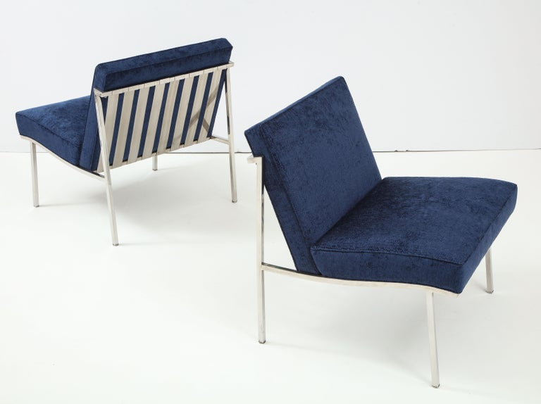 Sinuous and sculptural pair of armless lounge chairs in polished stainless steel with new upholstery. Designed by William Armbruster and produced by Edgewood Furniture, circa 1954. Armbruster's work was widely recognized in its day, including MoMA