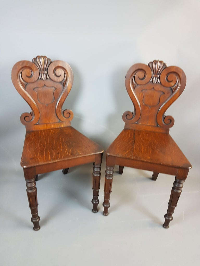 A very nice pair of 19th century William IV style oak hall chairs. These chairs are in very nice solid condition with only one leg having an old brass bracket on it, the quarter sawn grain on the oak gives a lovely decorative appeal to this pair.