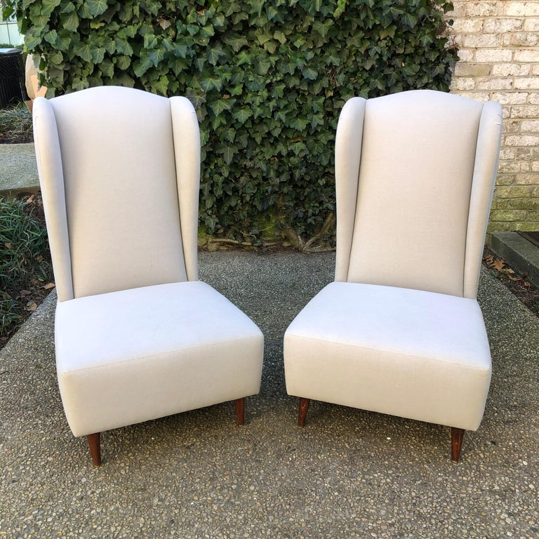 Unique pair of armless wing back slipper chairs newly upholstered in natural linen.