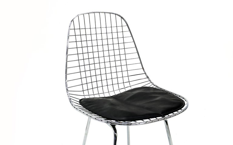 Two wire bar stools designed by Charles and Ray Eames, manufactured by Herman Miller. Polished chrome frames with black leather (not vinyl) seat pads. These were bought new several years ago and barely if ever used.