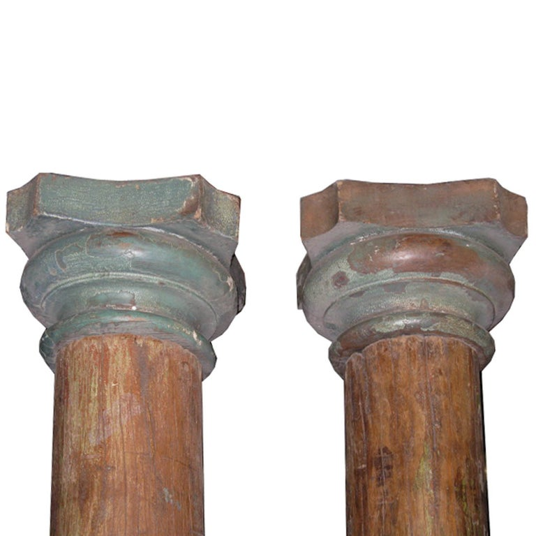 Pair of beautiful wood columns from a Haveli in Gujarat, India. The columns have carved wood capitals and stone bases. Originally used to adorn an entry in a traditional Indian Haveli. Assembly required.