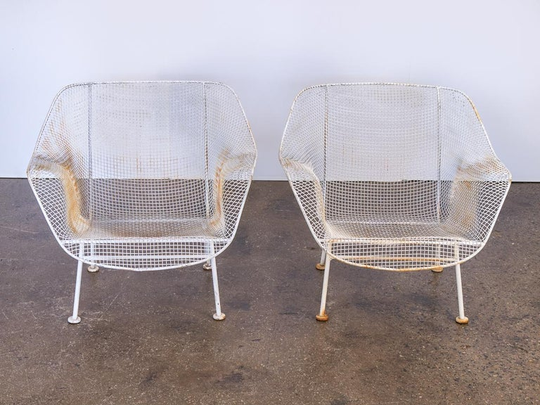 1950s Pair of Woodard Sculptura garden lounge chairs. These hard to come by chairs feature a low-slung design for patio or deck lounging. The wrought iron frames and woven mesh steel seats are strong and can stand all weather. White enamel finish