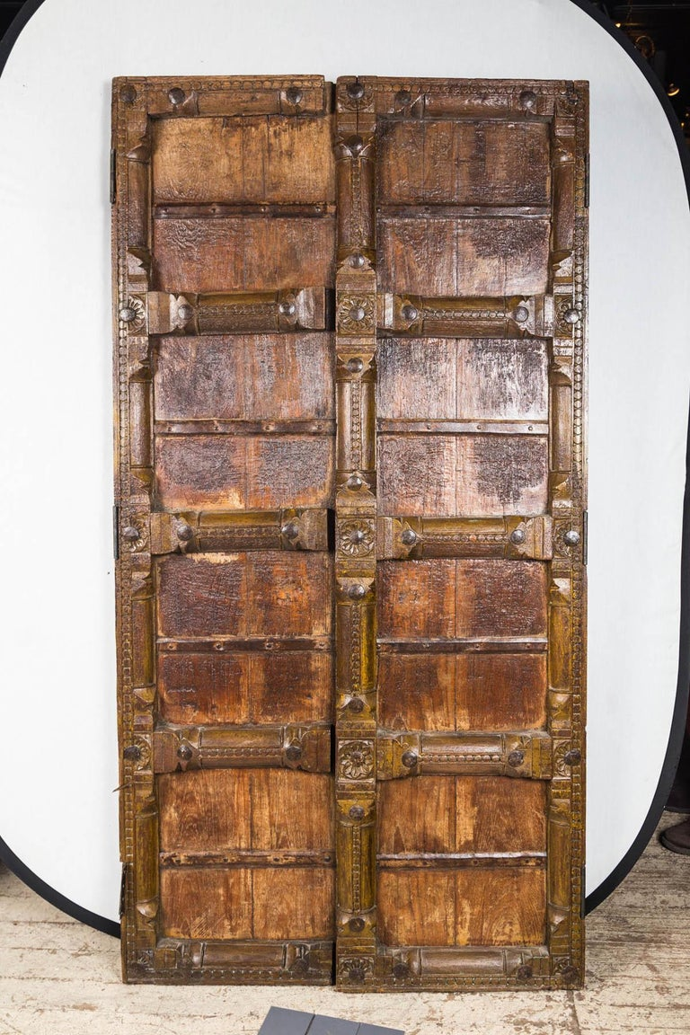 This pair of doors are handmade and heavy. There is no lock, never was. Iron straps and nails can be seen on the back. There is no evidence of any pulls. Cross bars and verticals are simply carved. There are hinges on both.