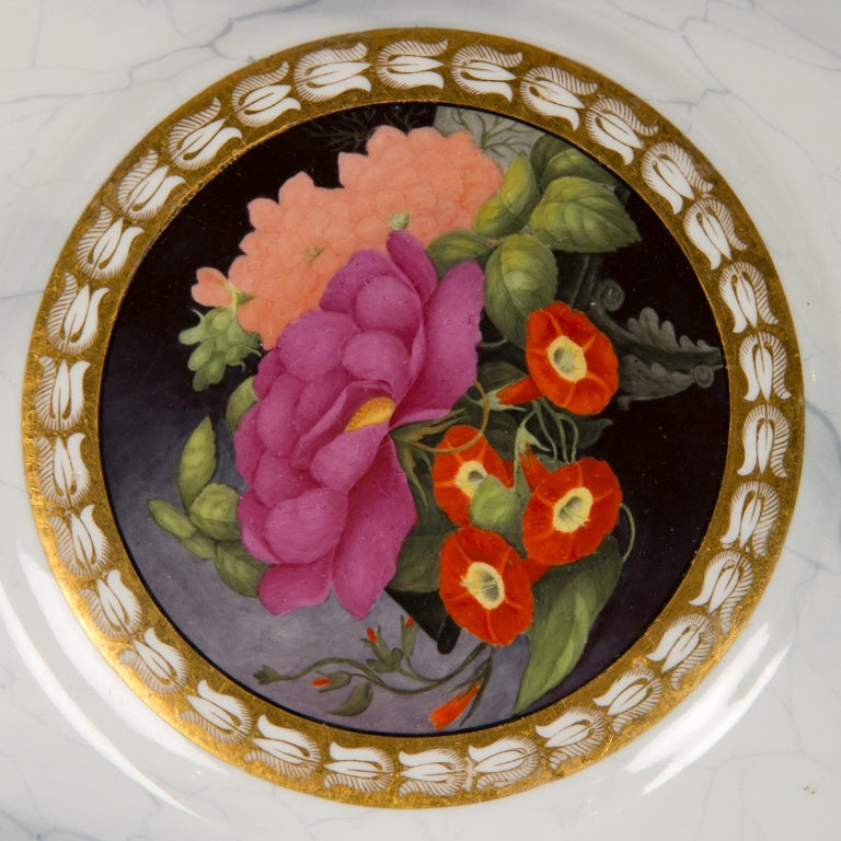 We are delighted to present this pair of Worcester plates with bright hand-painted flowers set against a dark purple ground in the center of each plate. Made circa 1810 they show freesia, a pink rose, a purple peony, peach colored dahlias, and other