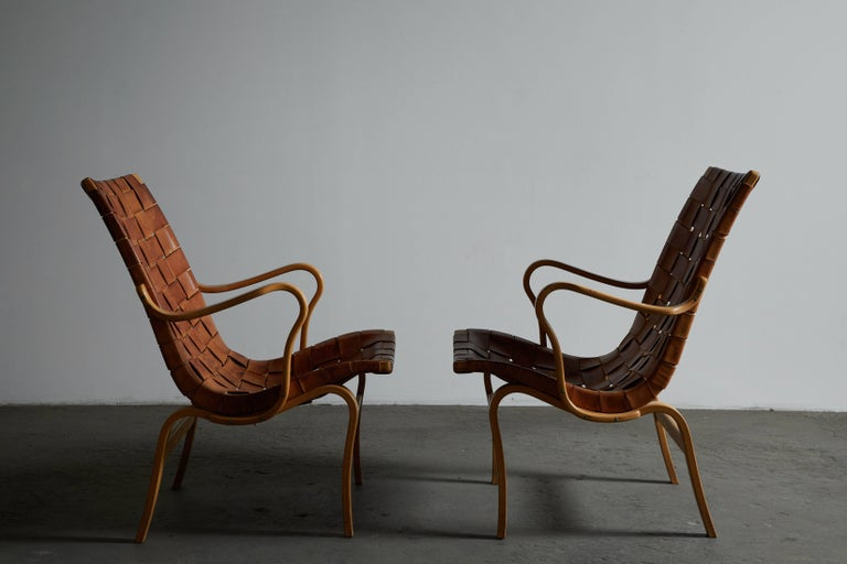 Pair of patinated leather armchairs by Bruno Mathsson. Made in Sweden, circa 1970s.   Signed with branded manufacturer's marks to stretcher.
