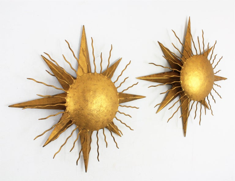 Spectacular pair of Brutalist hand-hammered iron gilded sunburst wall sconces this beautiful pair of light fixtures have a star shaped base with a sunburst shade with rays in different sizes. They could work also as ceiling light fixtures, Spain,