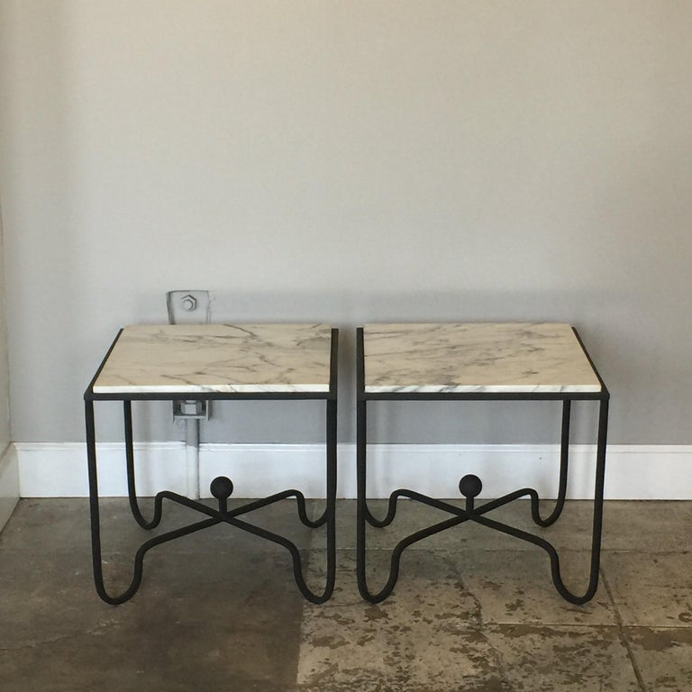 Chic pair of wrought Iron and marble 'Entretoise' side tables by Design Frères. Matte black wrought iron bases with polished white veined marble tops.