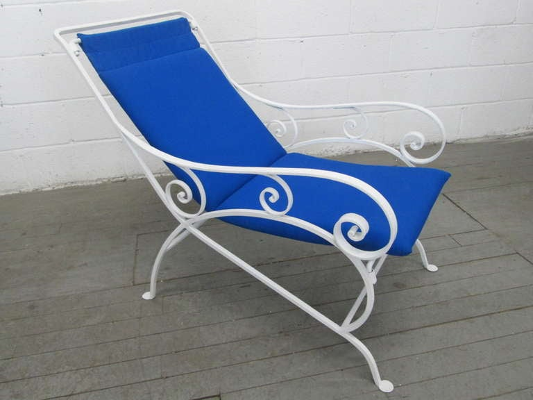 Stunning pair of wrought iron lounge chairs. Chairs have newly upholstered fabric and are very comfortable. Great look for deck, poolside, patio or garden.
