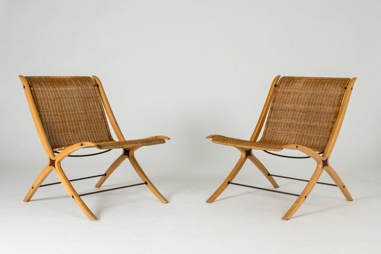 """Pair of amazing """"X"""" lounge chairs by Peter Hvidt and Orla Møllgaard, made from laminated beech and rattan. Cool detail of darker wood inlays at the cross section of the legs and back. Beautiful, unbroken lines."""