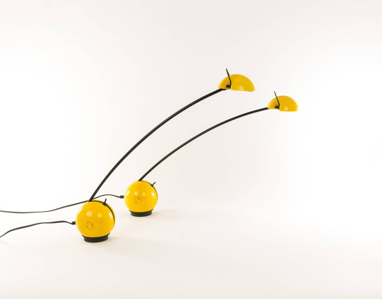 Pair of yellow Alina table lamps produced by Italian manufacturer Valenti. Playful lamp with ingenious system that allows for adjustment in different positions.  The spherical base contains the transformer and rests on a separate holder that is