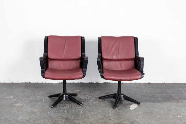 Pair of Yrjo Kukkapuro swivel side or desk chairs in black molded plastic with newly upholstered wine colored leather cushion.  Made in Finland by Haimi. .