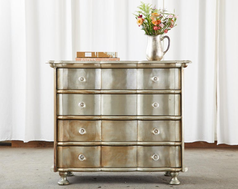 Dazzling pair of commodes, chests, or dressers featuring a hand-wrapped polished zinc sheet metal veneer. The zinc metal is secured with hundreds of hand-hammered tiny nails in a painstaking laborious process. The chests are crafted from a wood case