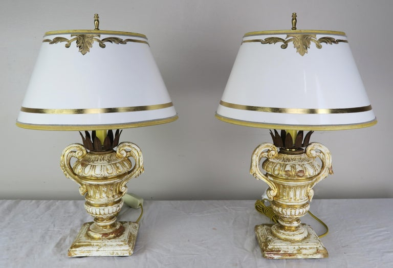 Pair of candleholders from the early 1900s. The handled urns have metal crown shaped bobeches that hold a candle that has been newly electrified into lamps. The lamps are crowned with hand painted parchment shades that coordinate perfectly with the