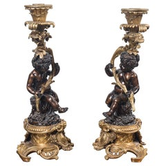 Pair Patinated and Gilt Bronze Putti Candlesticks