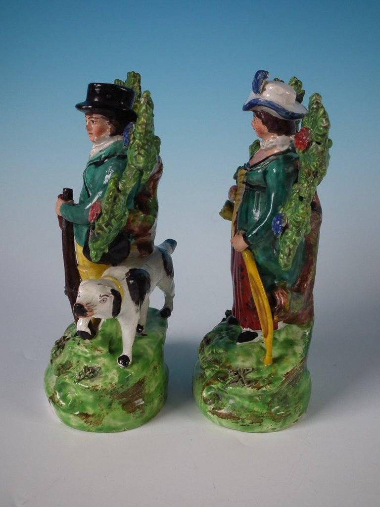 Pair of Staffordshire pottery pearlware bocage figures with a hunting theme which feature a huntsman with his dog and a female archer, stood on shaped bases. The pieces are titled, 'Sportsman' & 'Archer' to the fronts. Decorated 'in the round' -