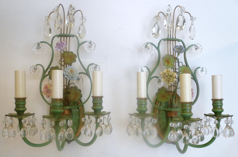 These neoclassical lyre back sconces are in the Louis XVI style, and feature hand painted porcelain flowers. They are made of enameled bronze with gilt highlights, and are hung with crystal drops. These sconces were purchased from the estate of Drue