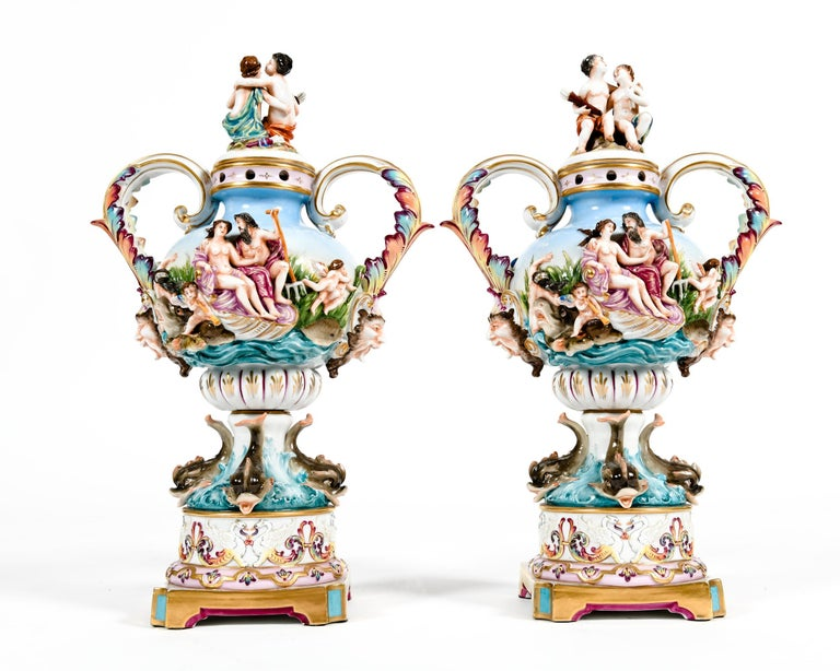 "Pair of porcelain covered urns / decorative pieces decorated with exterior bacchantic design detail scenes. Each piece is in excellent antique condition. Minor wear consistent with age / use. Maker's mark blue crowned ""N"