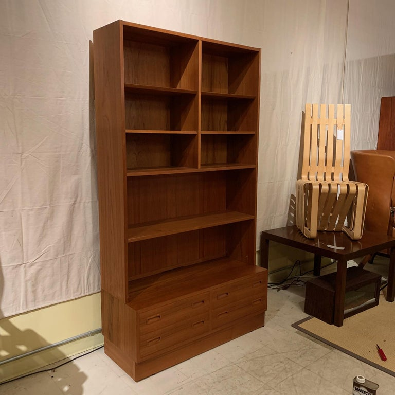 A versatile teak bookcase with five adjustable shelves and one fixed shelf. base consists of four drawers. Labeled Poul Hundevad and also has Danish Control label.
