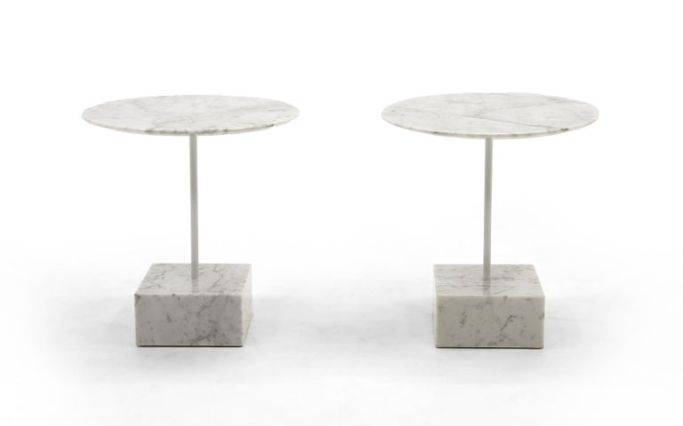 Pair of white marble side tables designed by Memphis Milano founder, Ettore Sottsass for Ultime Edizioni, Italy, 1990. Heavy square marble bases with beautifully beveled round marble tops. A lacquered steel support connects the top to the base. Very