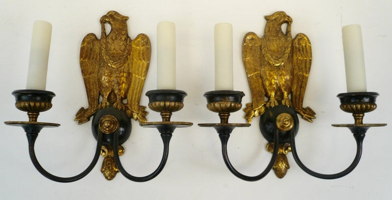 This handsome pair of gilt and patinated bronze two-light sconces feature mirror image eagles, and pinecone finials. They are newly re-wired, and ready for use.