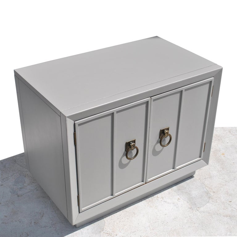 Pair of Mid-Century Modern nightstands Regency style side tables  Restored in a dove grey with brass pulls. Ample storage with shelving.   Measures: 28.25