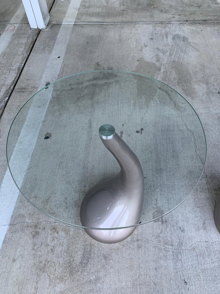 A pair of sinuous resin base tables with round glass tops. These tables came from a Movie Prop supply house. The top glass screws on to the base. We have has the bases re-painted in a glossy pewter silver color. The glass tops have some minor marks