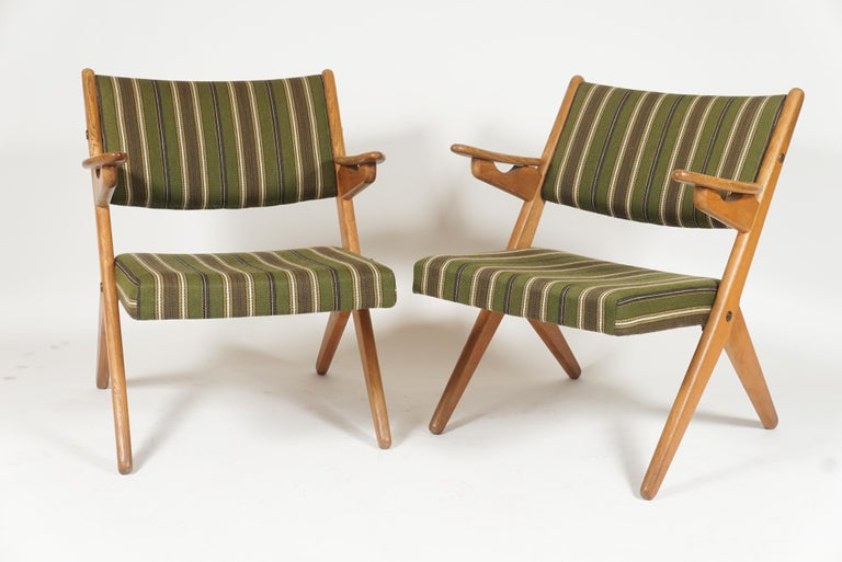 Sleek pair of Scandinavian easy lounge chairs reminiscent of Folke Ohlsson scissor chairs and Hans Wegner sawbuck chairs. Oak framed with original cushions and fabric. Great midcentury lines in a sleek pair of comfortable chairs.
