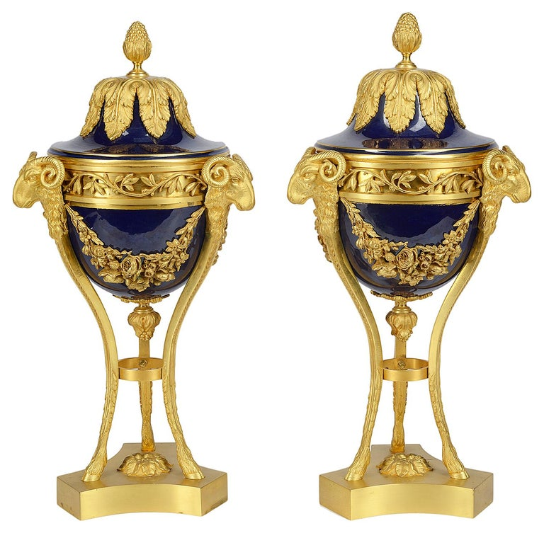 A good quality pair of early 20th century Sevres style lidded porcelain and gilded ormolu mounts. Each with classical foliate, swag and ram's head detail and raised on hoof feet.