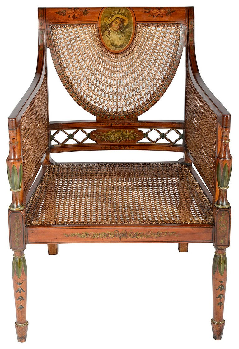 A very good quality pair of late 19th century satinwood, Sheraton Revival library Bergere chairs, each with classical hand painted decoration to the show wood of flowers, leaves and musical instruments, the top rails having paintings of ladies in