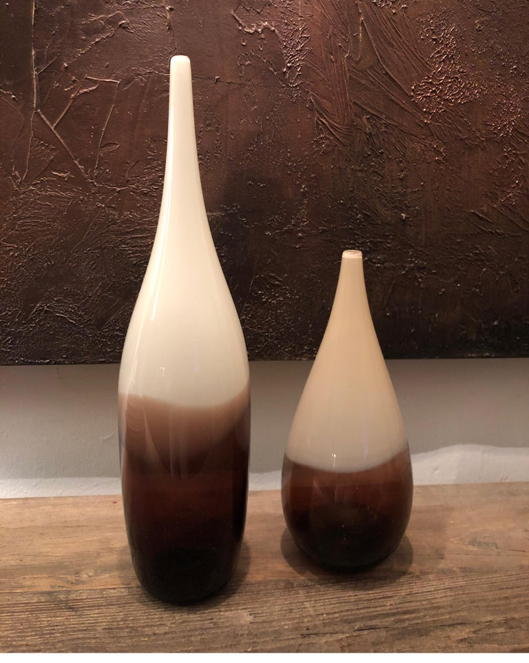 Pair of hand blown and shaped in lead free crystal. Murano inspired glass with transparent white/off-white and amber layers. One vase measures 16