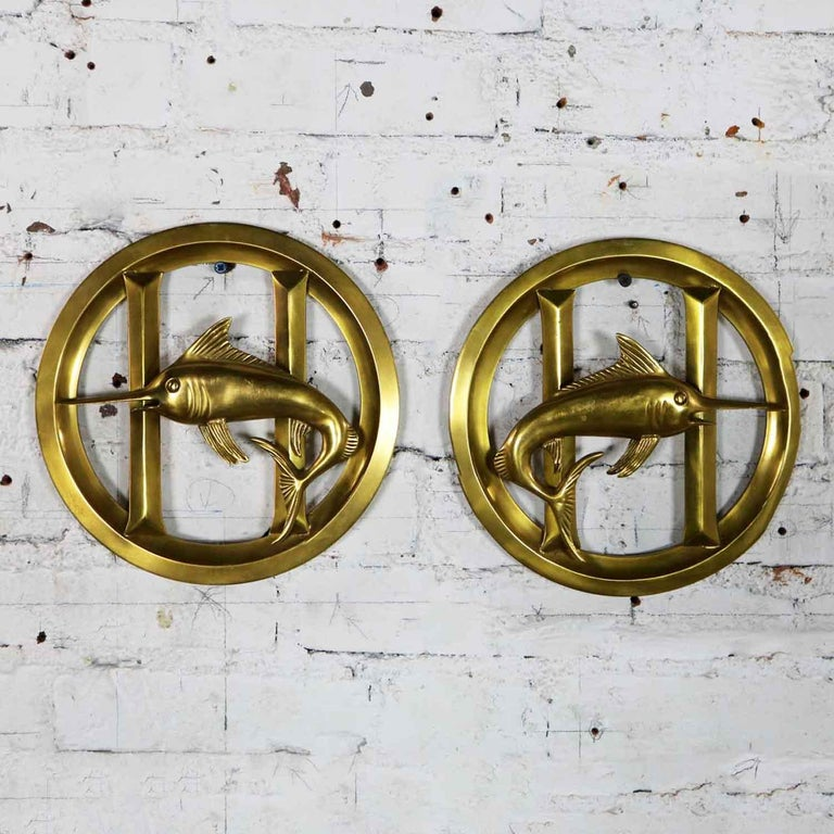 Wonderful nautical decor. A pair of solid brass porthole cover grills with an applied solid brass swordfish design. They are in fabulous vintage condition and ready to use. They are priced as a set, circa 20th century.  Ahoy Matey! I'm sure you
