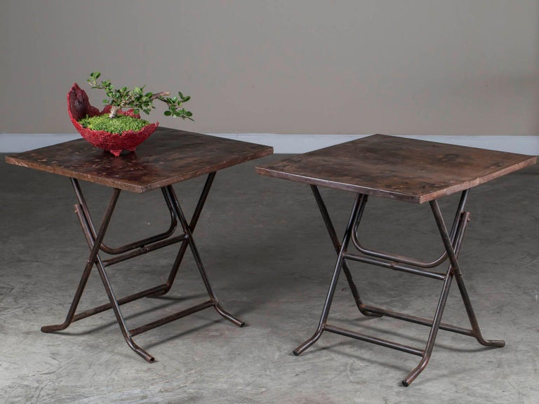 A super functional and good looking pair of square metal folding tables with folded edges and tubular legs found in Asia. The scale of these tables are perfect for bedside or sofa as they easily accommodate a lamp and objects across their surface.