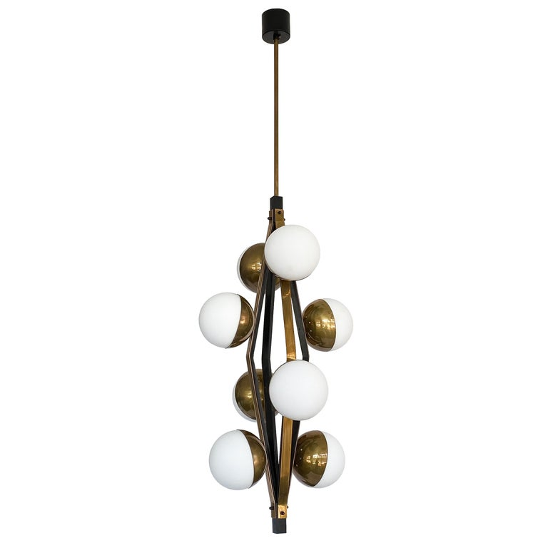 Stilnovo patinated brass pendant chandeliers with eight satin oplaine glass globes, Italy, circa 1950s. Priced individually. These Italian chandeliers feature a geometric diamond shaped open framework in blackened iron and beautifully patinated