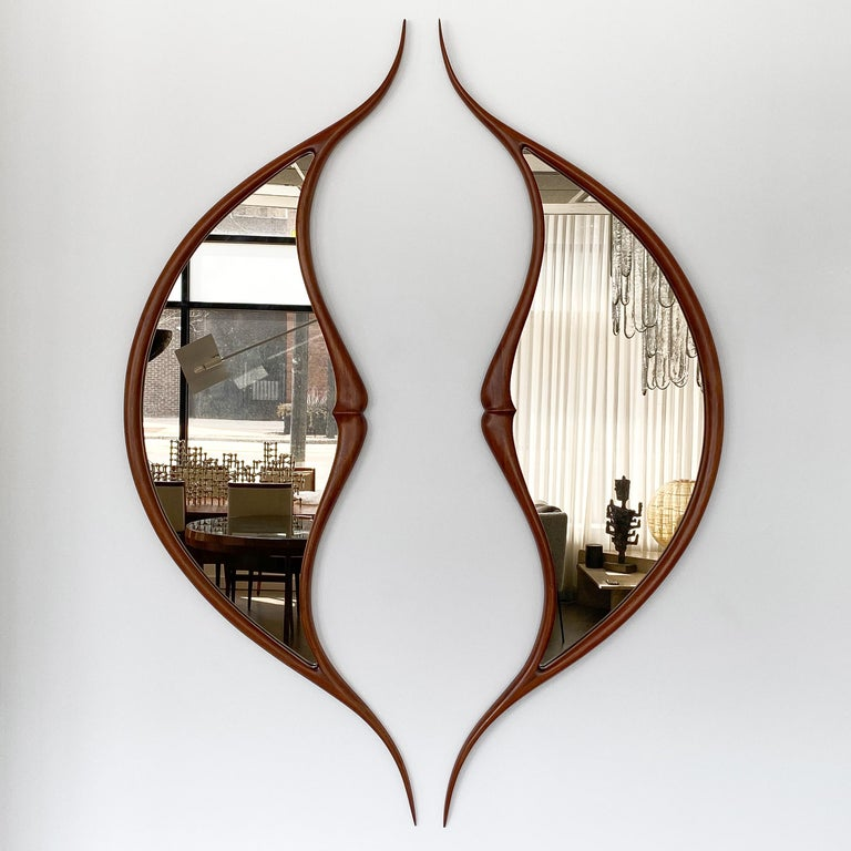 Pair of American Studio Craft Movement carved sculptural walnut wall mirrors by sculptor Mark Levin, circa 1970s. The two large separate mirrors are opposing forms to create an abstracted kiss. Mark Levin often describes the inspiration of his work