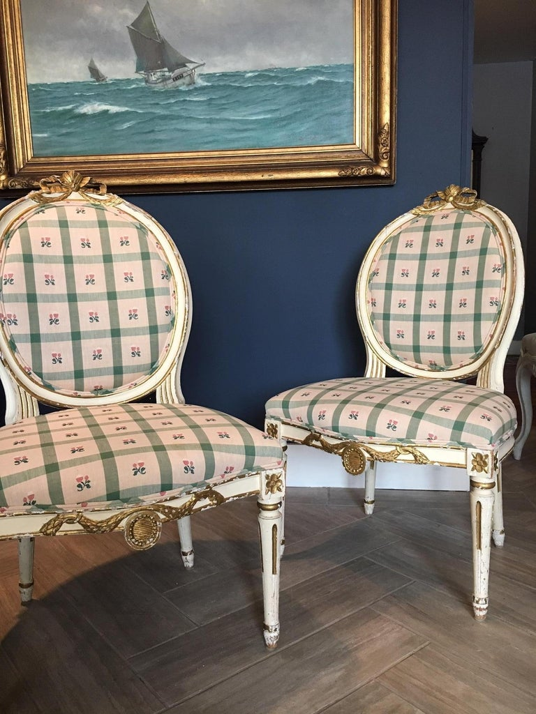 Gorgeous pair of Swedish side or salon chairs, painted and parcel gilt, in the Gustavian or Louis XVI style, 19th century. Crested by carved ribbons, with medallion motifs. Beautifully curved back.