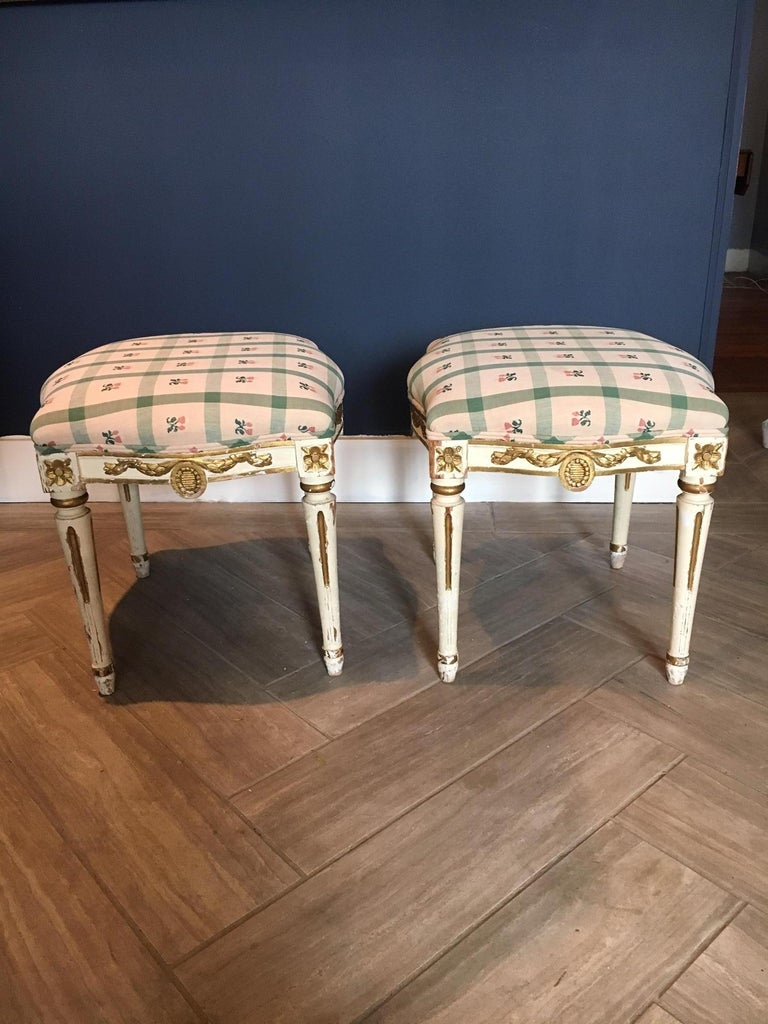 Gorgeous pair of Swedish stools/ tabourets, painted and parcel gilt, in the Gustavian / Louis XVI style, 19th century. Medallion motifs.   Forms a set with pair of side chairs/ salon chairs, sold separately.