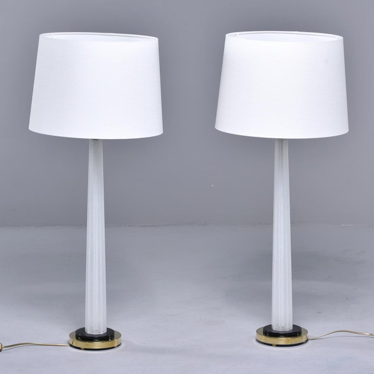 Pair of tall, slightly tapered white Murano glass table lamps attributed to Seguso. Contrasting base of black with brass fittings. Newly wired for US electrical standards. Shades show are not included. Sold and priced as a pair.
