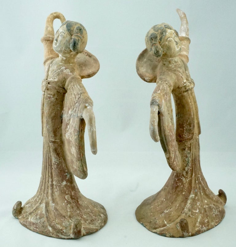 Period: Tang Dynasty (618 – 907 AD) terra-cotta over lead clay  A pair of delicate Tang Dynasty dancers with long sleeves. Both ladies are wearing a long flowing dress with flared sleeves. Their facial features are accentuated with black and white