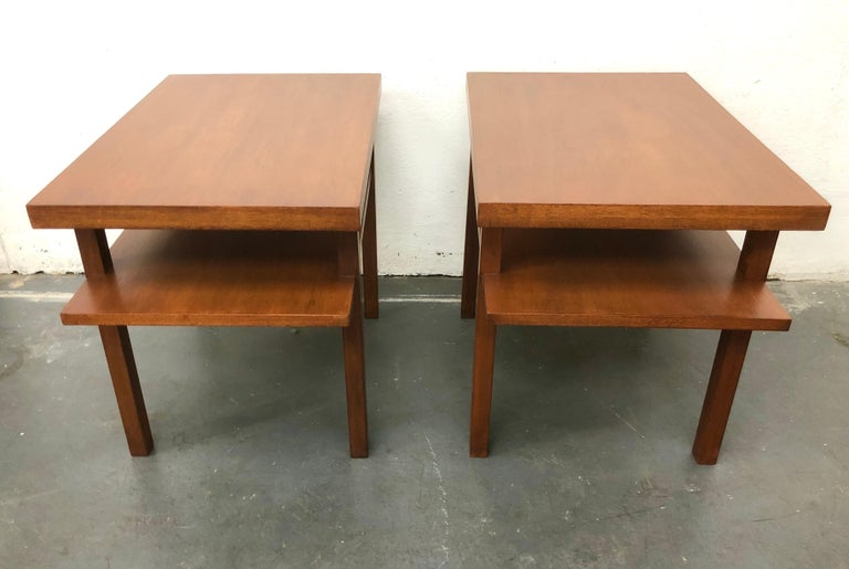 An early architectural Gibbings design, c. 1940s, in mahogany. The slightly elongated bottom shelf disrupts the overriding simplicity. Widdicomb labels.  Table tops are 28