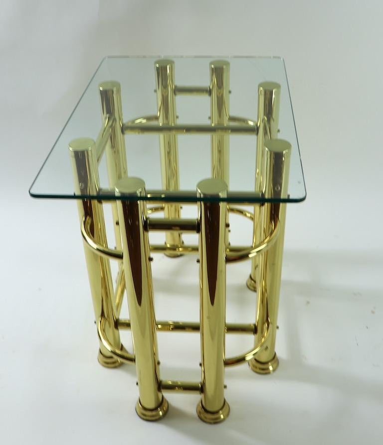 Pair of Mod Style tubular brass based tables with thick (.50 inch) plate glass tops. Architectural constructivist design bases in shiny brass finish, chic, stylish, clean and ready to use. Both tables are in very good original condition, showing
