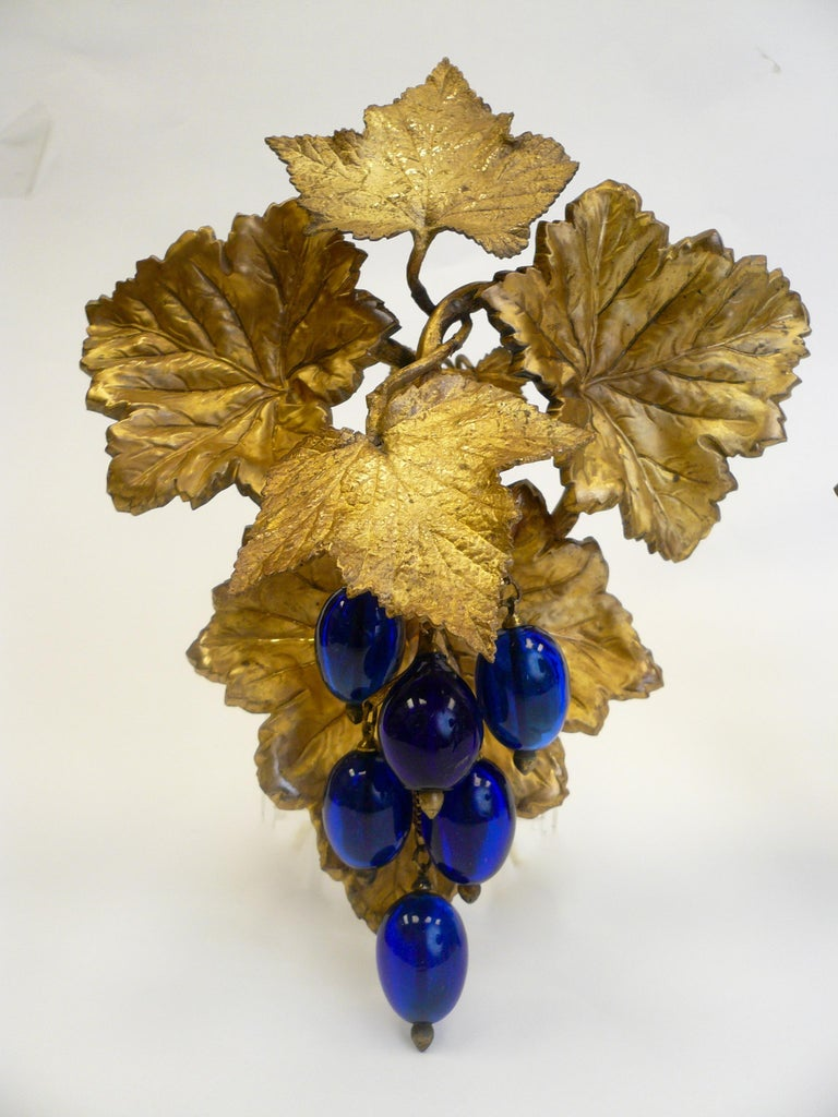 This impressive pair of vintage motif Victorian curtain tiebacks feature cast and repousse gilt brass grape leaves, and cobalt blue blown glass grapes.