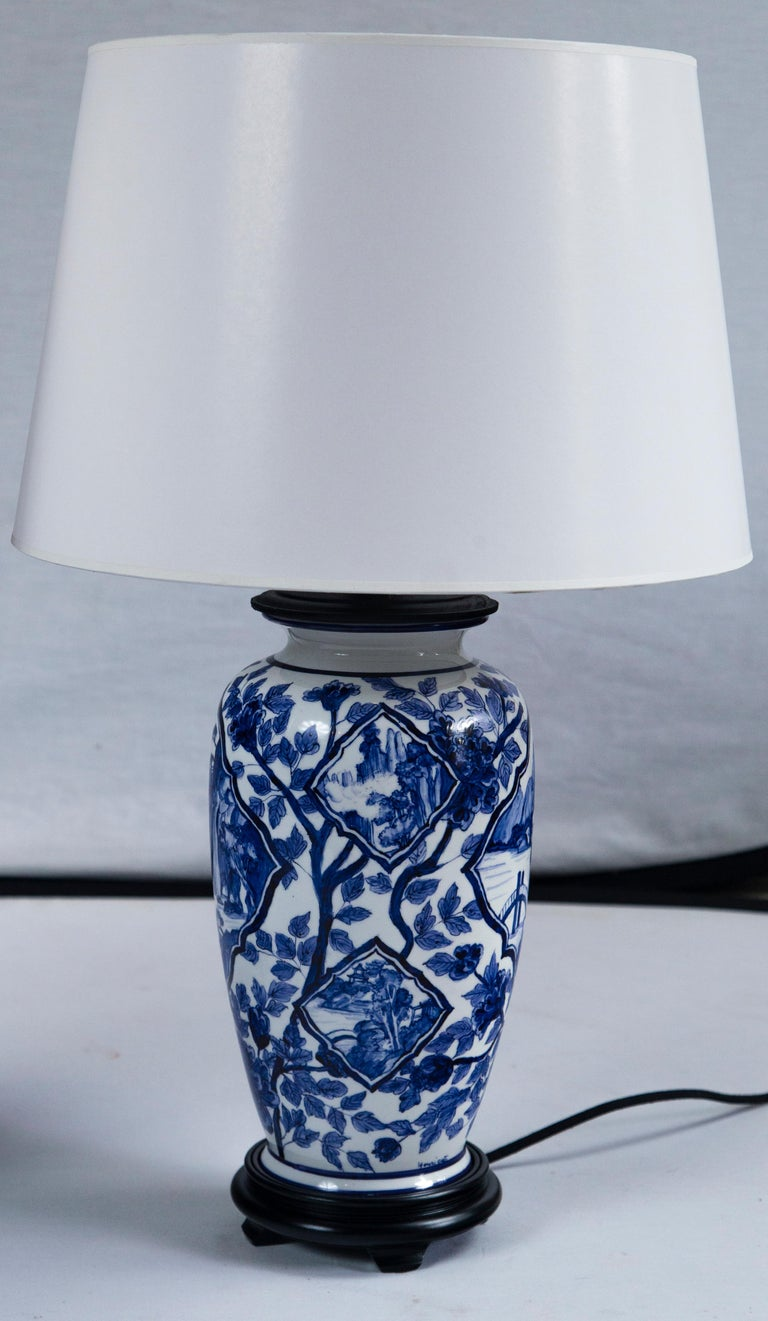 Pair vintage Asian ceramic lamps, 20th century. Overall blue and white floral design with landscape motifs. Newly wired and mounted.