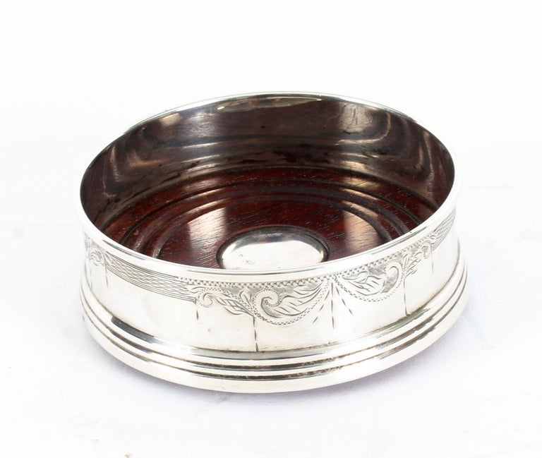 A superb pair of 20th century sterling silver wine coasters, by W Broadway & Co, Birmingham, 1994.  Of circular form with engraved scroll decoration to the sides on a ring turned polished wood base with sterling silver boss in
