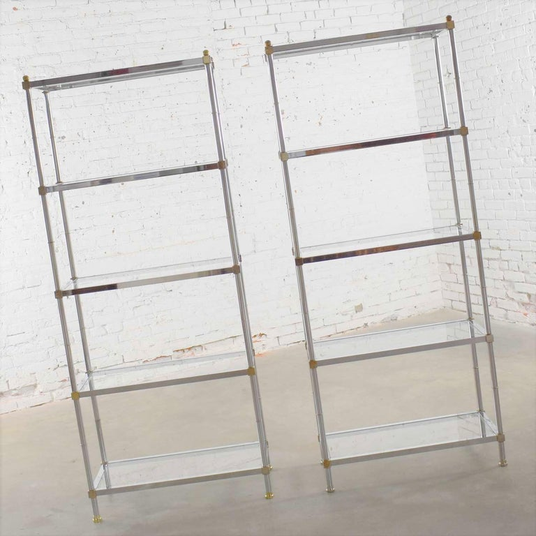Handsome pair of vintage chrome, brass, and glass étagère display shelves done in the manner of Maison Jansen. They are both in great vintage condition. They do have scratches and marks as you would expect with age and use. We call that patina.