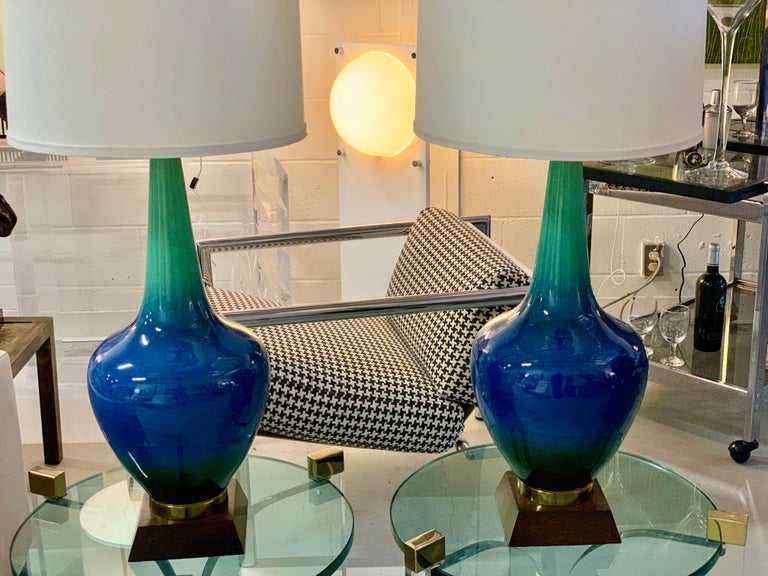 A vintage pair of midcentury ceramic lamps in a beautiful blue green glaze. These lamps have been rewired with new fittings. The bases have age wear, losses to the finish and nicks. The ceramic bodies are in good age appropriate condition. Shades