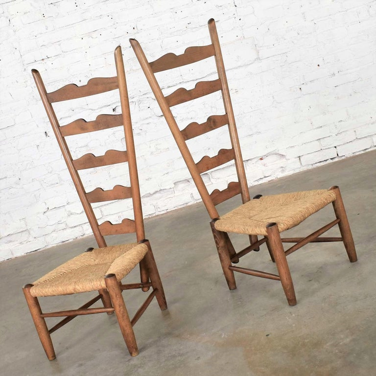 Handsome pair of Italian fireside ladderback chairs designed by Gio Ponti for Casa e Giardino. They are in fabulous original condition with a lovely age patina to the wood and the rush seats. No outstanding flaws. Three of the plugs which cover